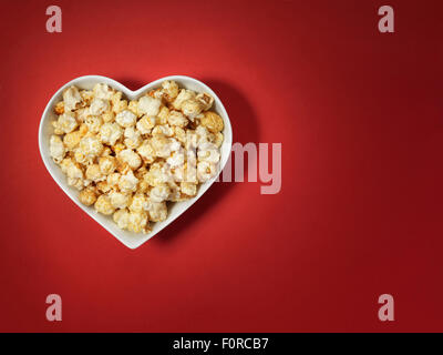 shot of cinema style popcorn in a heart shaped bowl on a bright red background with spotlit, vignette style lighting and offset