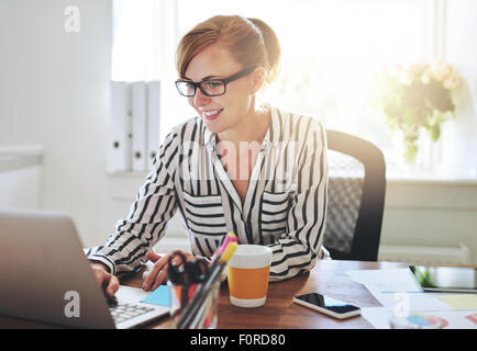 Successful female entrepreneur with a new online business working from home on her computer typing in data - Stock Photo