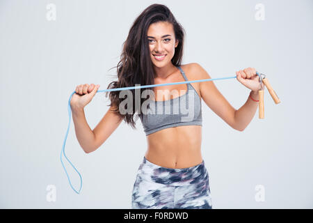 Portrait of a charming woman holding skipping rope isolated on a white background - Stock Photo