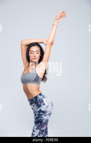 Portrait of a charming fitness woman posing isolated on a white background - Stock Photo