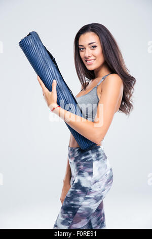 Portrait of a happy fitness woman holding yoga mat isolated on a white background - Stock Photo