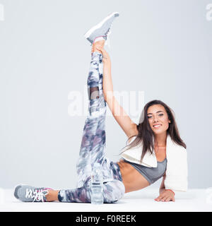 Portrait of a charming sports woman stretching legs on the floor isolated on a white background - Stock Photo