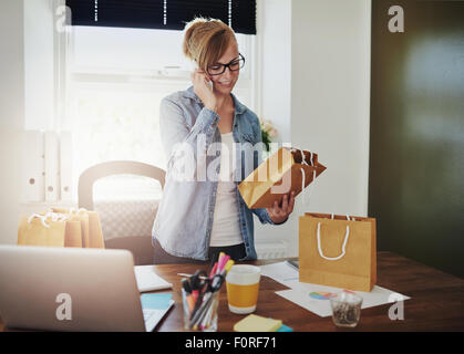 Motivated businesswoman placing orders on the phone for the packaging for her new online web based store as she - Stock Photo