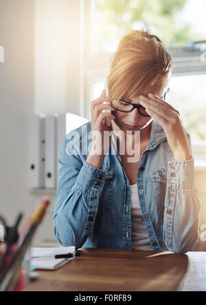 Concerned female entrepreneur talking on a phone as she sits at her desk in her home office with her head resting - Stock Photo
