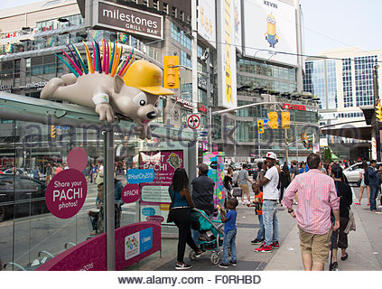 Advertisement for the Toronto 2015 Pan/Parapan Am Games: the children designed mascot Pachi sits on top of a public - Stock Photo