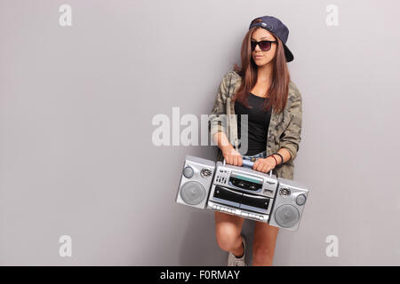 Cool teenage girl in hip hop outfit holding a ghetto blaster and leaning against a gray wall - Stock Photo