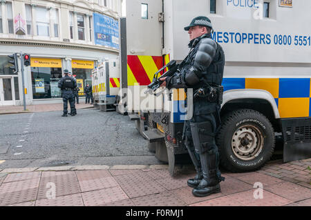 Armed PSNI police officer holds a Heckler & Koch G36C automatic machine gun on a street in Belfast as armoured cars - Stock Photo