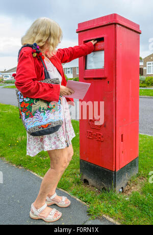 Middle aged woman posting a letter in a red rectangular letter box in England, UK. - Stock Photo