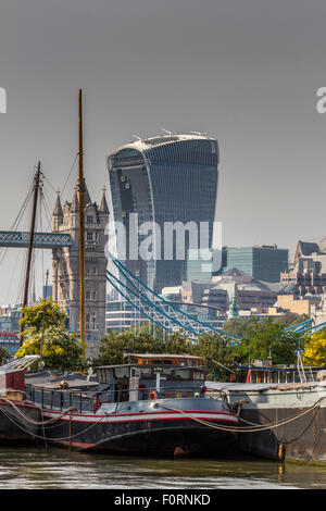 A barge On The river Thames withThe Walkie Talkie Building or 20 Fenchurch St & Tower Bridge side by side as seen - Stock Photo