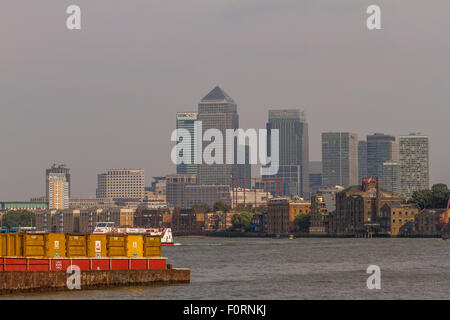The Skyscrapers of Canary Wharf tower over The River Thames as seen from the riverbank in Bermondsey, London - Stock Photo