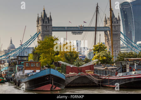 Houseboats and barges moored near Tower Bridge in Bermondsey  with 20 Fenchurch St , The Walkie Talkie Building, - Stock Photo