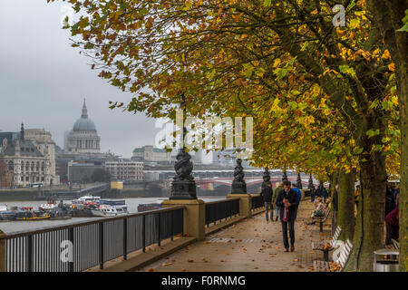 People walking along The River Thames on The South Bank during Autumn with St Paul's Cathedral in the distance , - Stock Photo