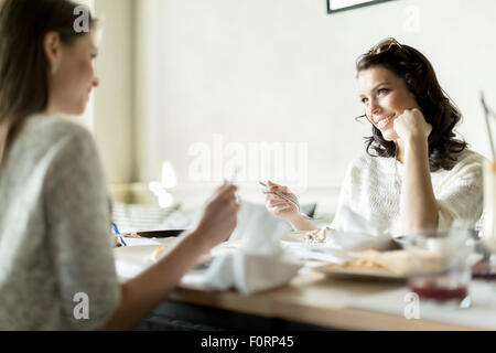 Two gorgeaus ladies eating in a restaurant while having a conversation - Stock Photo