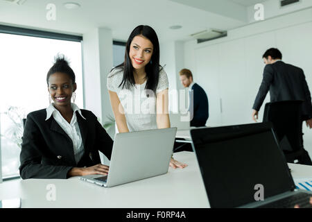 Black and white businesswomen looking at a laptop and working in a neat office environment - Stock Photo