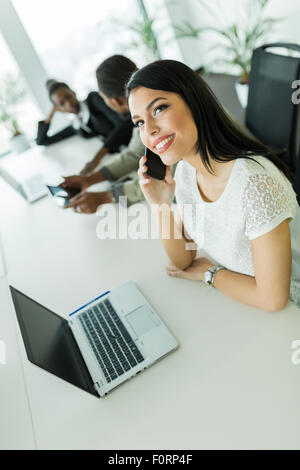Happy and beautiful young businesswoman sitting at an office table and talking on her mobile phone - Stock Photo