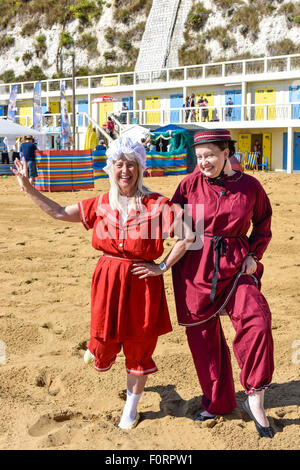 Two women wearing traditional Victorian bathing costumes on the beach at Viking Bay in Broadstairs, Kent. - Stock Photo