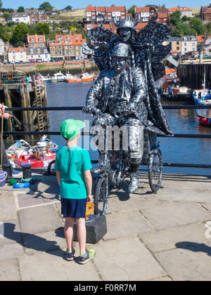 Small boy watching a man posing as a  living statue on a tricycle and with a devil on his back in Whitby North Yorkshire - Stock Photo