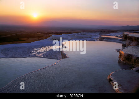 Hot springs and travertines (terraces of carbonate minerals left by the flowing water) at sunset, Pamukkale, near - Stock Photo