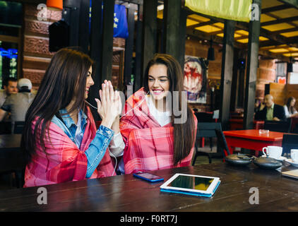 Two young and beautiful girls having fun in cafe - Stock Photo