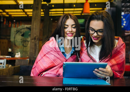 two close friends watching something on a tablet - Stock Photo