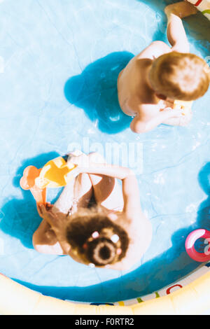 Young children playing with toys inside an inflatable pool during summertime - Stock Photo