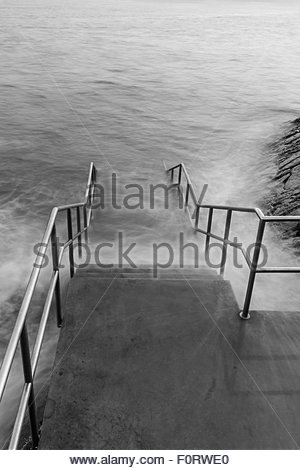 An image of the new steps that recede into the sea at Barry Island, shot with a long exposure to artistically blur - Stock Photo