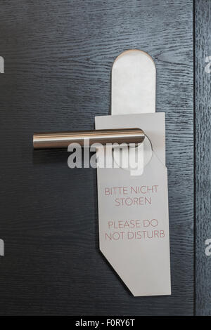 Hotel Door sign 'Please do not disturb' in German and english - Stock Photo