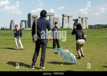 A family of East Asian tourists view the stone circle at Stonehenge on Salisbury Plain, England UK. The mother takes - Stock Photo