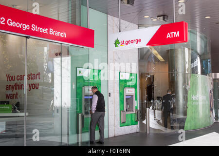 Man using a cashpoint ATM at St George bank branch in Sydney city centre,australia - Stock Photo