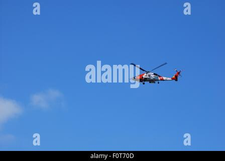 A brightly-colored helicopter flying with a deep blue sky as the background. - Stock Photo