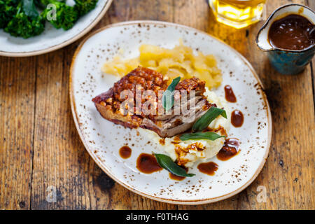 Pork belly with crackling, mashed potatoes, apple sauce and deep fried sage leaves - Stock Photo