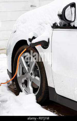 Electric car plugged in to an outlet recharging outdoors in winter snow - Stock Photo