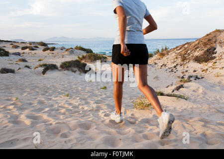 Female Indian jogger jogging on a beach - Stock Photo