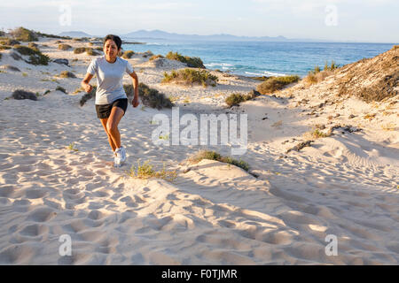 Young Indian female jogging outdoors by the sea - Stock Photo