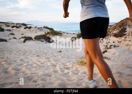 Asian Indian woman exercising outdoors on a beach - Stock Photo