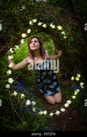 Fairytale fantasies: A young woman teenage girl alone by herself kneeling down wearing a dress in woodland surrounded - Stock Photo