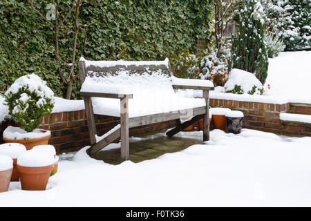 Snow covered garden bench on a patio in winter - Stock Photo