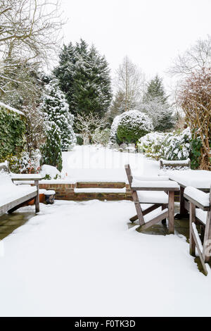 Landscaped English garden covered in snow in winter - Stock Photo