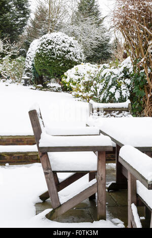 Snow covered patio furniture in a garden in winter - Stock Photo