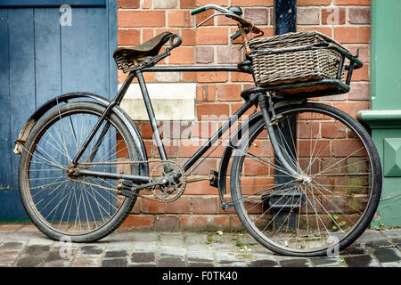 Old retro cycle with basket leaning against a brick wall - Stock Photo