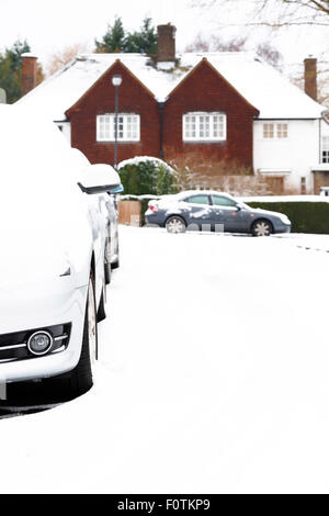 Parked cars in an English village in England in winter - Stock Photo