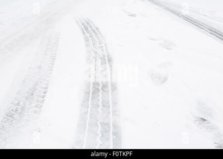 Closeup of tire tracks on a street with snow - Stock Photo