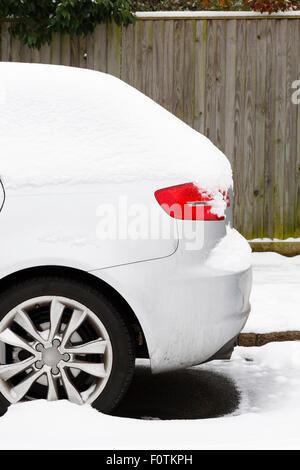 Side of car covered in snow parked on a British road in winter - Stock Photo