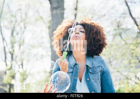 Front view of mid adult woman blowing bubbles, eyes closed, looking up - Stock Photo