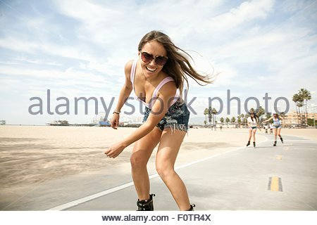 Portrait of young woman, outdoors, skating - Stock Photo