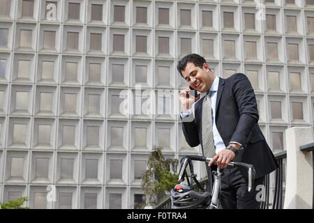 Mid adult business man holding bicycle, making telephone call using smartphone - Stock Photo