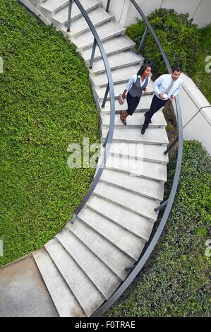 High angle view of business people descending spiral stairway - Stock Photo