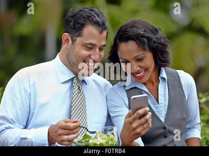 Business people sitting side by side enjoying a salad on lunch break, looking at smartphone, smiling - Stock Photo