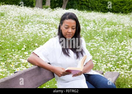 Mature woman sitting on park bench reading book - Stock Photo