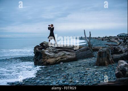 Woman looking through binoculars from large driftwood tree stump on beach - Stock Photo